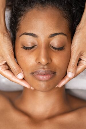 African american woman at spa getting face massage. Beautiful young woman getting head massage in spa and wellness center. Close up face of black girl with closed eyes relaxing during beauty treatment. 版權商用圖片 - 132031177