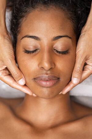 Donna afroamericana alla stazione termale che ottiene massaggio facciale. Bella giovane donna che ottiene massaggio alla testa nel centro termale e benessere. Chiuda sul fronte della ragazza nera con gli occhi chiusi che si rilassano durante il trattamento di bellezza.