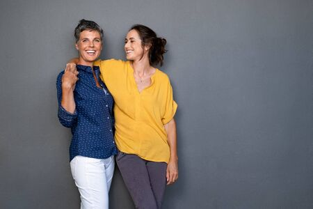 Mature happy women embracing each other against grey wall with copy space. Happy laughing ladies in smart casual standing on gray background. Cheerful middle aged woman with hand on shoulder of her stylish friend.