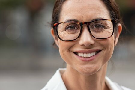 Portrait of mature businesswoman wearing eyeglasses and looking at camera. Close up face of cheerful woman with spectacles smiling outdoor. Confident beautiful entrepreneur wearing specs with a big grin. Stok Fotoğraf