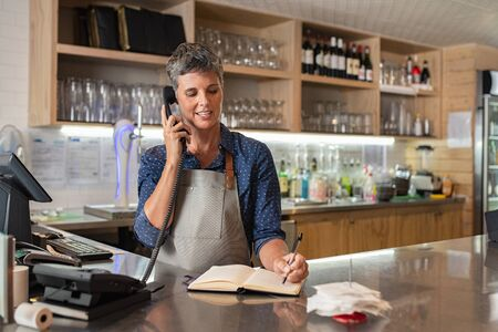 Barista woman taking orders over the phone at counter. Mature woman in grey apron writing on customer book while talking over phone in cafeteria. Waitress writing takeaway lunch while using telephone.