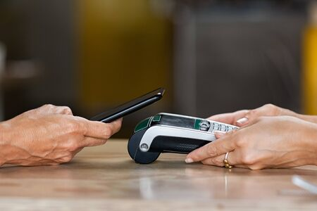 Closeup of woman hand paying a bill through smartphone using NFC technology. Closeup of hand holding pos terminal to receive payment using mobile phone. Customer using mobile to make payment with contactless. Imagens - 132031187