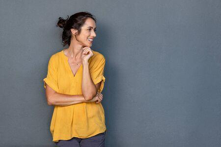 Rijpe mooie Latijns-vrouw geïsoleerd op een grijze achtergrond op zoek aan kant met kopie ruimte. Portret van een positieve brunette vrouw die lacht en wegkijkt. Gelukkige dame van middelbare leeftijd die tegen een grijze muur staat en denkt Stockfoto