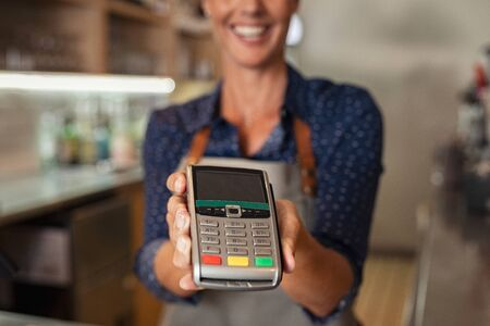 Waitress standing at cash counter holding an electronic card payment machine. Close up of mature woman hand holding wireless terminal POS at coffee shop. Happy smiling owner showing NFC technology machine to customer across counter to make payment. Imagens - 132031229