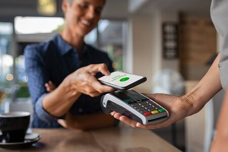 Mature woman paying bill through smartphone using NFC technology in a restaurant. Satisfied customer paying through mobile phone using contactless technology. Close up hands of mobile payment at a coffee shop.