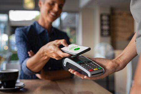 Reife Frau, die Rechnung über Smartphone mit NFC-Technologie in einem Restaurant bezahlt. Zufriedener Kunde, der mit kontaktloser Technologie per Mobiltelefon bezahlt. Schließen Sie die Hände des mobilen Bezahlens in einem Café.