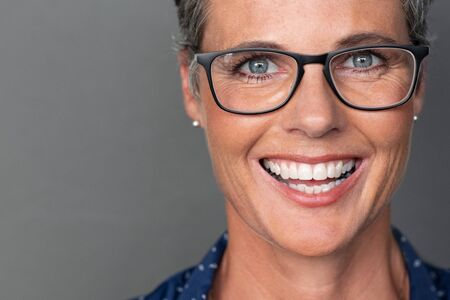 Portrait of happy mature woman wearing eyeglasses and looking at camera. Closeup face of smiling senior woman against grey wall wearing spectacles. Successful businesswoman feeling happy wearing glasses on gray background with copy space. Фото со стока