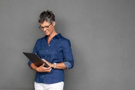 Smiling mature businesswoman wearing spectacles while using digital tablet against grey background with copy space. Successful senior business woman surfing internet on digital tablet on gray wall. Beautiful middle aged woman checking email on laptop.