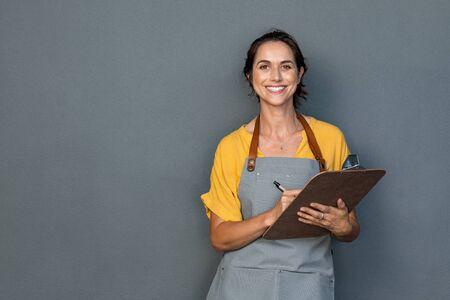 Gelukkig lachend serveerster die bestellingen aanneemt die op grijze muur zijn geïsoleerd. Rijpe vrouw die een schort draagt terwijl ze op het klembord schrijft en tegen een grijze achtergrond staat met kopieerruimte. Vrolijke eigenaar klaar om de bestelling van de klant op te nemen terwijl hij naar de camera kijkt. Klein bedrijfsconcept. Stockfoto