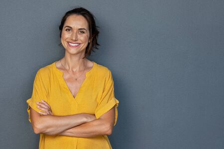 Confident mature woman with crossed arms in casual clothing standing against grey background with copy space. Successful smiling woman with toothy smile looking at camera. Beautiful positive businesswoman standing.