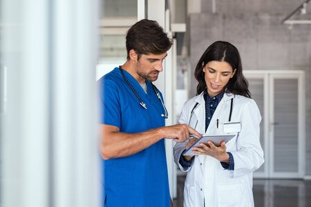 Doctor and nurse discussing over a medical report in hospital. Female mature doctor and nurse checking clinical report of patient online. Healthcare staff having discussion in a hallway of private clinic.