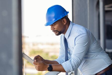 Mature manager using digital tablet on construction site. Serious african engineer checking email at building site wearing blue hardhat. Architect working on digital tablet leaning at balustrade. Standard-Bild - 134439482