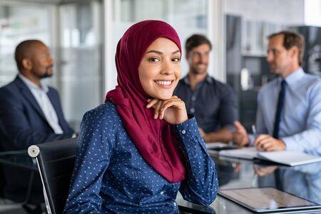 Schöne arabische Geschäftsfrau, die Kamera betrachtet und lächelt, während sie im Büro arbeitet. Porträt der fröhlichen islamischen jungen Frau, die Hijab bei der Sitzung trägt. Muslimische Geschäftsfrau, die am Konferenztisch mit multiethnischen Kollegen im Hintergrund arbeitet und sitzt.