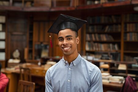 Happy african student in graduation cap standing in library and looking at camera. Portrait of a satisfied and proud graduate young man. Handsome african american student in formal clothing wearing mortar board.