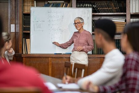 Senior teacher explaining math formulas written on whiteboard in library while college students sitting on table understanding the concept. Happy mature woman lecturer clearing doubts to students in class. Professor teaching to high school guys and girls.