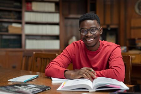 Portrait of university student doing homework in school library and smiling. Happy high school student looking at camera while studying for exam. African american clever guy with open book sitting at desk with copy space.