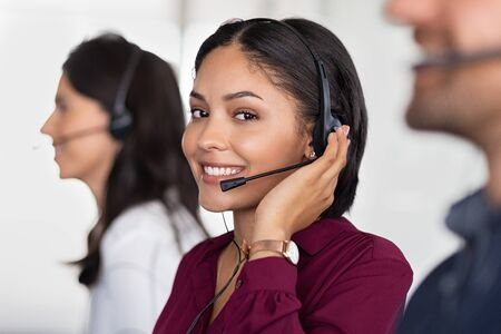 Smiling beautiful woman working in call center as telemarketing operator. Smiling customer support agent wearing headset at office, working while looking at camera. Middle eastern girl working as telephone operator with her colleagues. Imagens