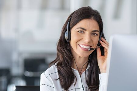 Call center agent with headset working on support hotline in modern office with copy space. Portrait of mature positive agent in conversation with customer over headset looking at camera. Consulting and assistance service customer support.