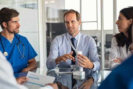 Mature man with professional doctors in hospital showing medicine bottles. Confident representative pharmaceutical showing new medicines to a team of doctor and nurse. Specialist showing bottle of pills and explaining drug dosage to a group of specialist in meeting room.