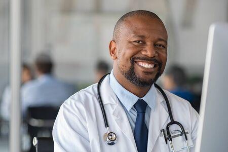 Glücklicher lächelnder afrikanischer Doktor, der Kamera in der Arztpraxis betrachtet. Porträt des Arztes des schwarzen Mannes, der im modernen Krankenhaus am Laptop arbeitet. Selbstbewusste und zuverlässige reife Krankenschwester, die einen Computer verwendet, um den medizinischen Bericht des Patienten zu analysieren.