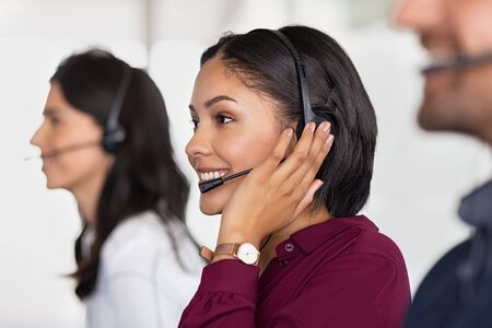 Multiethnic colleagues working in a call center. Team of business people sitting in a row working in a call center. Smiling customer support operator at work. Smiling young middle eastern woman with headset working at helpdesk.