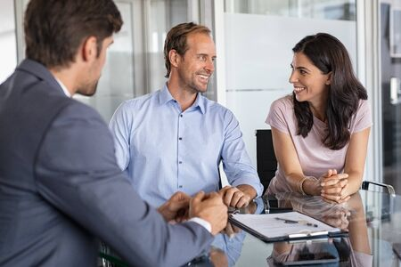 Mature smiling couple meeting financial advisor for investment at modern office. Financial consultant presents bank investments to confident man and happy woman. Middle aged couple consulting their bank agent about savings plan. Foto de archivo
