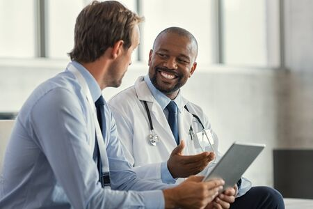 Two mature smiling doctors having discussion about patient diagnosis, holding digital tablet. Successful african surgeon discussing case after positive result. Representative pharmaceutical discussing with african happy doctor about new medicine. Standard-Bild