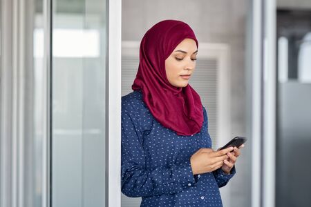Young muslim businesswoman leaning against glass wall using smartphone. Islamic business woman in hijab using mobile phone in modern office. Arabic serious girl texting on cellphone to send email message.