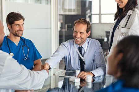 Happy businessman shaking hands with doctor in meeting room. Doctor and representative pharmaceutical shaking hands in medical office. Cheerful salesman with new medicines shaking hands with senior doctor in hospital with medical team sitting at conference table. Stockfoto