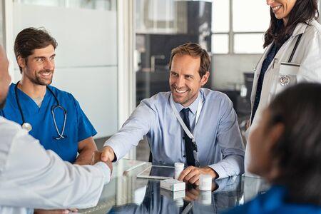 Uomo d'affari felice che stringe la mano al medico nella sala riunioni. Medico e rappresentante farmaceutico si stringono la mano in studio medico. Venditore allegro con nuovi farmaci che stringono la mano a un medico anziano in ospedale con un'equipe medica seduta al tavolo della conferenza. Archivio Fotografico
