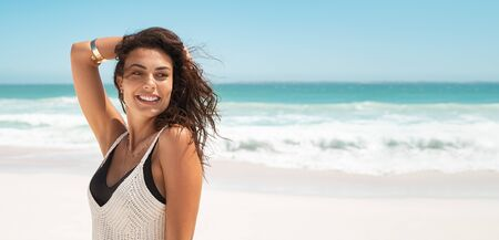 Latin stylish woman relaxing at tropical beach during summer vacation. Portrait of carefree tanned girl relaxing at sea with copy space. Young smiling woman enjoying breeze in a sunny day while looking away.
