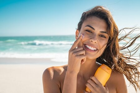 Beautiful young woman at beach applying sunscreen on face and looking at camera. Beauty latin girl enjoying summer holiday while applying suntan lotion at sea. Portrait of happy woman with healthy skin applying sunblock on cheek.