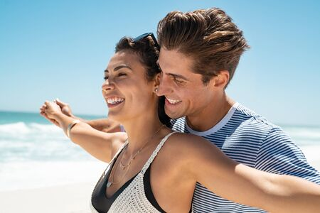 Romantic couple with outstretched arms enjoying summer at beach. Cheerful husband and beautiful wife during honeymoon at sea. Happy smiling young couple with outstretched arms at beach on a bright sunny day.