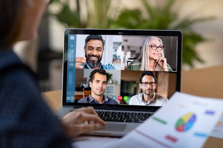 Back view of business woman talking to her colleagues about business plan in video conference. Multiethnic business team using laptop for a online meeting in video call. Group of buinessmen and businesswomen smart working from home. Standard-Bild