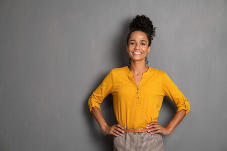 Portrait of young african woman standing with hands on waist and looking at camera. Confident stylish latin girl smiling isolated against grey background. Beautiful cool woman with copy space standing on gray wall. Banque d'images