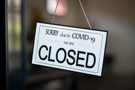 Shop closed due to Covid-19 outbreak lockdown. Temporarily closed sign for coronavirus in a small business activity due to quarantine measures in public places and restaurant. We are closed sign board through the glass of store or cafe window. Banque d'images