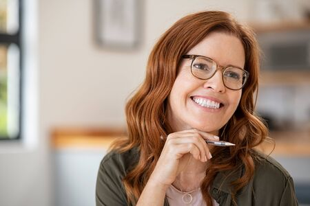 Thoughtful mature woman with hand on chin wearing eyeglasses and working at home. Cheerful mid writer wearing spectacles and holding pen thinking. Successful happy blogger contemplating and writing with copy space.