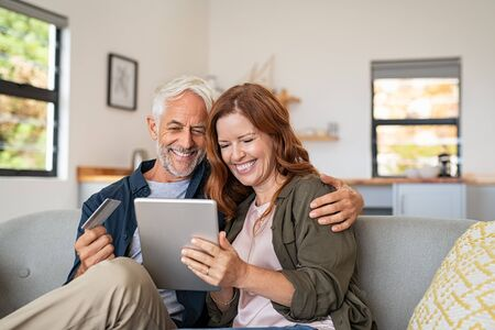 Happy mature couple sitting on sofa and doing online shopping on digital tablet at home. Senior husband and smiling wife paying bills online. Joyful middle aged couple doing online payment on digital tablet, copy space. Banque d'images