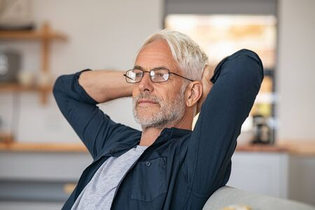 Senior man relaxing at home and thinking with hands behind head. Mature man wearing eyeglasses while resting at home and looking away. Retired old man sitting on couch, thinking about the future. Banque d'images