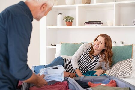 Senior man packing stuff into suitcase at home. Happy middle aged couple packing clothes and accessories into travel bag, preparing for honeymoon vacation. Cheerful woman lying on bed with man arranging clothes in luggage for travel.