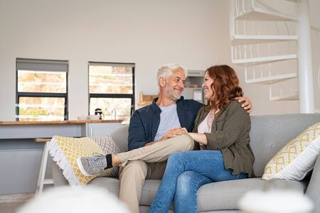 Retired mature couple sitting on couch together. Senior husband with smiling wife sitting on sofa and embracing while looking at each other. Happy old couple in love holding hands. Banque d'images
