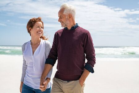 Happy senior couple walking on the beach in a sunny day. Smiling mature couple looking at each other on white beach during sunset with copy space. Retired man in love with his beautiful wife relaxing during vacation.