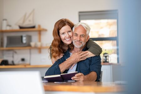 Portrait of happy mature couple at home looking at camera. Romantic wife embracing senior husband from behind while laughing together. Portrait of beautiful woman in love hugging  old man in perfect harmony. Banque d'images