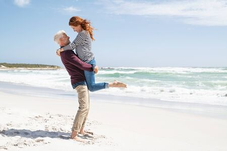 Mature couple hugging on the beach on a sunny day with copy space. Happy wife hugging her husband at the beach with her feet off the ground. Loving senior man lifting beautiful woman above the ground hugging her on the beach with sea in the background.