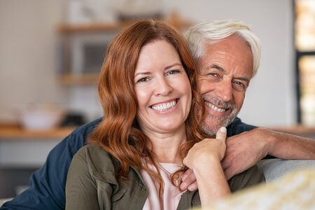 Portrait of middle aged couple hugging and looking at camera. Close up face of happy mature couple having fun at home. Senior man embracing his beautiful wife on the couch while looking at camera together.