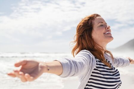 Happy redhead woman relaxing with arms outstretched at beach on a bright morning with eyes closed. Beautiful middle aged woman felling free at sea. Smiling cheerful mid woman relaxing at the seaside with copy space.