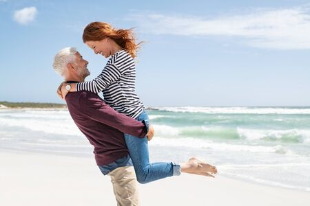 Mature couple hugging on the beach on a sunny day. Senior active man lifting beautiful mid woman on the beach with sea in the background and copy space. Happy retired couple hugging at seaside while looking at each other.