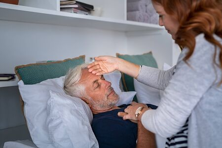 Mature woman checking fever temperature of senior man lying on bed with closed eyes. Old husband resting at home feeling sick while wife measure the fever by touching forehead. Elderly man feeling the seasonal symptoms of the flu.
