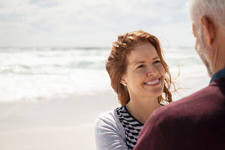 Lovely mature couple in conversation at sea. Rear view of old man with laughing beautiful wife relaxing during summer holiday. Portrait of beautiful redhead woman embracing and looking her husband on beach with copy space.