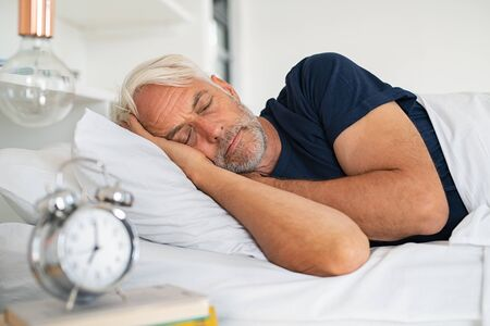 Old tired man sleeping on bed at home. Senior man with white hair in deep sleep on soft pillow at home. Mature healthy guy lying on side resting at home while sleeping.